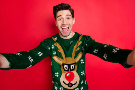 Close up photo of funny funky crazy man make selfie enjoy newyear christmas celebration wear deer reindeer trendy sweater isolated over red color background