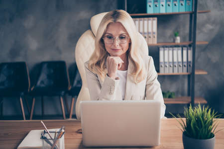Photo of freelancer business woman pondering on searching of way of development of her corporation sitting before laptop using internet Stock Photo
