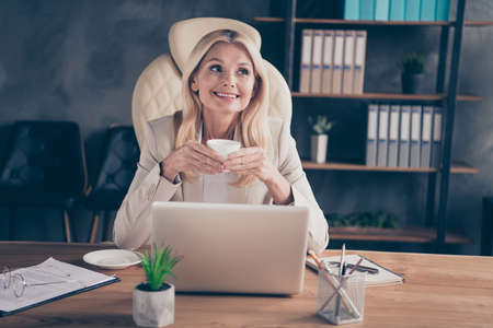 Photo of cheerful positive ceo holding cup of tea with hands sitting in front of computer having relax with glasses taken off