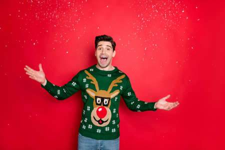 Portrait of his he nice attractive handsome cheerful cheery glad guy wearing green deer sweater having fun throwing snow isolated over bright vivid shine vibrant red color background Standard-Bild
