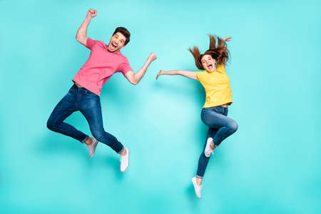 Full length body size view of nice attractive crazy funky cheerful carefree couple jumping in air having fun fooling rejoicing dancing isolated on bright vivid shine vibrant green turquoise background