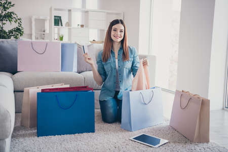 50 off online payment concept. Full body photo of positive cheerful girl hold debit card sit floor carpet with many packages enjoy purchase show her new stylish sweater indoors in showroom 写真素材