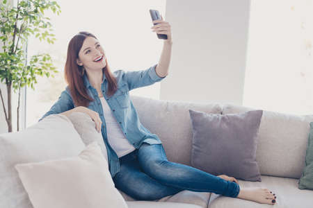 Photo of amazing lady telephone in hands making selfies for social network blog sitting comfy sofa wearing jeans clothes apartment indoors Stock fotó