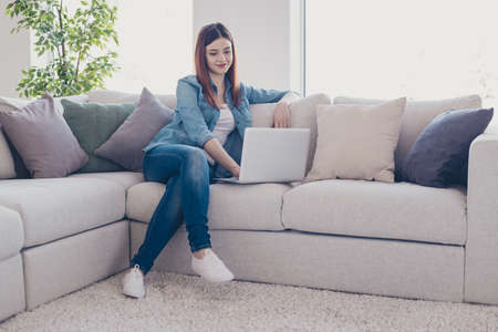 Photo of business lady holding notebook working at home speaking skype with colleagues sitting sofa wearing jeans outfit apartment indoors Stock fotó