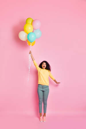 Vertical full length photo of astonished emotional funny teenager hipster holding many baloons in hand feeling she can be blown up to the sky in clouds in summer day isolated pastel color background