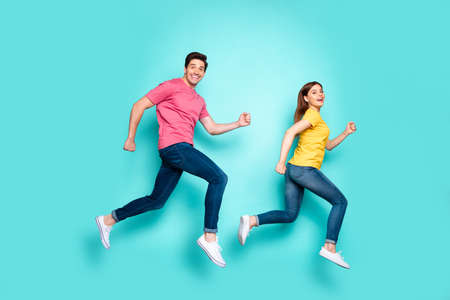 Full length body size profile side view of nice attractive funny cheerful cheery couple running fast speed in air having fun isolated over bright vivid shine vibrant green turquoise background 免版税图像