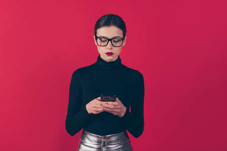 Portrait of her she nice-looking attractive pretty fashionable serious, concentrated girl using device gadget isolated on maroon burgundy marsala red pastel color background