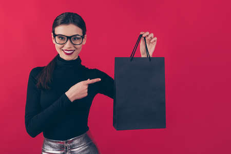 Portrait of her she nice-looking attractive pretty charming cheerful cheery, glad girl showing black bag with new cool things isolated over maroon burgundy marsala red pastel color background