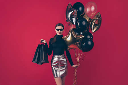 Portrait of her she nice-looking attractive pretty trendy cheerful lady holding in hands black, bags different air balls celebratory isolated on maroon burgundy marsala red pastel color background 免版税图像