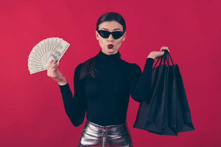 Portrait of her she nice-looking attractive trendy lady holding in hands black, bags large budget sum money finance expense pout lips isolated on maroon burgundy marsala red pastel color background 免版税图像