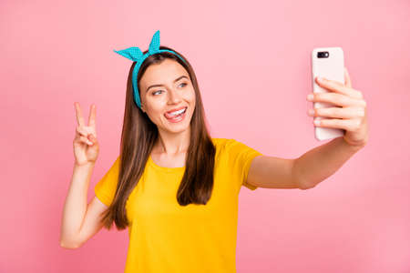 Portrait of charming woman, making photo v-sign using device wearing yellow t-shirt isolated over pink background Reklamní fotografie
