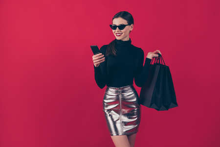 Portrait of her she nice-looking attractive pretty trendy cheerful lady using cell carrying, black bags order online new brandy things isolated over maroon burgundy marsala red pastel color background