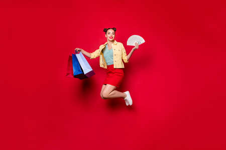 Full size photo of jumping shopaholic lady carrying many packs and bucks wear casual outfit isolated red background