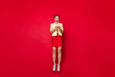 Full body photo of pretty jumping lady holding telephone hands wear casual outfit isolated red background