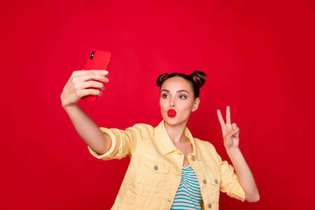 Photo of pretty lady holding telephone hands making selfies showing v-sign wear casual outfit isolated red background