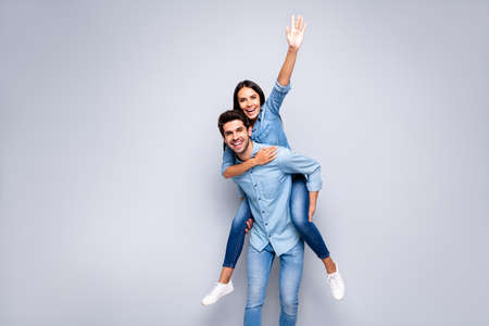 Hi there. Photo of funny guy and lady holding piggyback meet friends at street, waving arm wear casual jeans clothes isolated grey color background