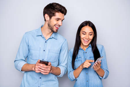 Portrait of his he her she nice attractive charming glad excited cheerful cheery couple holding in hands cell using 5g wi-fi connection, speed isolated over light white gray pastel color background
