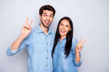 Portrait of his he her she nice attractive cheerful cheery funny couple, showing v-sign winking having fun isolated over light white gray pastel color background Stock Photo