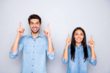 Portrait of his he her she nice attractive charming glad cheerful cheery confident couple wearing, casual pointing forefingers up copy space isolated over light white gray pastel color background Stockfoto