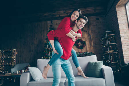 Portrait of romantic couple hug piggyback have christmas x-mas vacation, event near couch in house with newyear illumination lights indoors