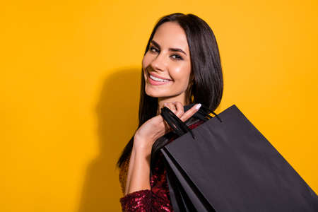 Photo of amazing lady in good mood holding packs in hands after long, waited shopping wear red dress isolated yellow color background