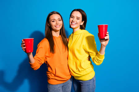 Photo of pretty two ladies, chilling at party raising plastic cups with beer wear casual bright yellow orange hoodies and jeans isolated blue color background