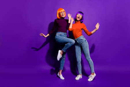 Full length body size view of two nice attractive charming cheerful excited glad girls wearing wigs dancing having fun isolated over bright vivid shine vibrant purple violet lilac color background