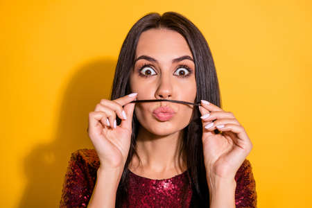 Photo of crazy lady making moustache with one curl pretending like guy wear shiny red dress isolated yellow color background