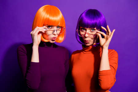 Close-up portrait of two nice attractive charming cute funny girlish, girls wearing wigs pout lips touching specs isolated on bright vivid shine vibrant purple violet lilac color background Imagens