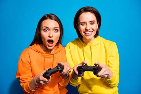 Photo of two funny ladies holding in hands joystick playing exciting, video game rejoicing wear casual bright yellow orange hoodies isolated blue color background