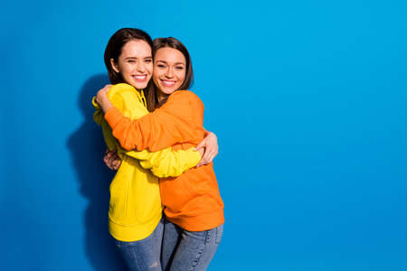 I missed you so much. Photo of two pretty girlfriends lady holding, each other in close hugs wearing casual bright hoodies jeans isolated blue color background