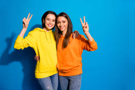 Photo of pretty two girlfriends lady showing v-sign symbols hugging, wearing casual bright hoodies and jeans isolated vibrant blue color background