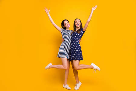 Full length photo of two amazing ladies celebrating beginning low shopping, prices season raising hands up wear summer casual trendy dresses isolated yellow background