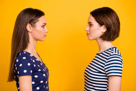 Profile photo of two amazing ladies standing opposite hate each other deciding who is better wear casual dotted and striped t-shirts isolated yellow background