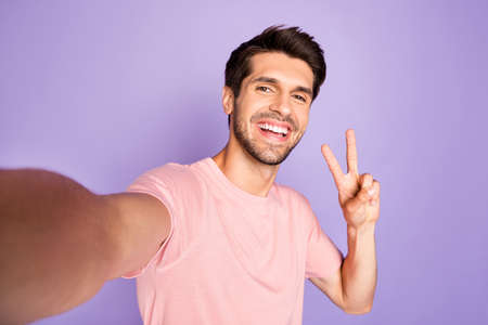 Self-portrait of his he nice attractive lovely cheerful cheery bearded brunet guy wearing pink tshirt showing v-sign isolated on violet purple lilac pastel color background Standard-Bild - 131267951