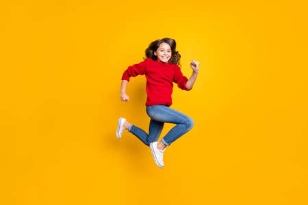 Full size photo of positive cheerful funky kid jump run after winter seasonal discounts wear stylish outfit white sneaker isolated over yellow color background
