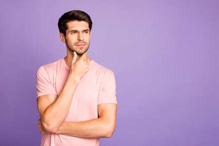 Portrait de son beau mec barbu brun à l'esprit concentré et attrayant portant un t-shirt rose créant une nouvelle idée touchant le menton isolé sur fond de couleur pastel violet violet lilas