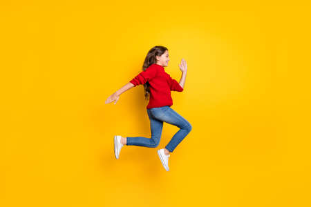 Full body profile side photo of positive cheerful model kid jump run fast speedy after black friday bargains wear red stylish pullover denim jeans white sneakers isolated over yellow color background