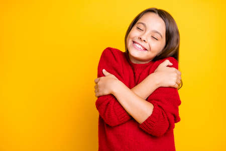 Portrait of peaceful calm kid hug embrace herself enjoy warm soft comfy sweater pullover wear red stylish lifestyle clothes isolated over yellow color background