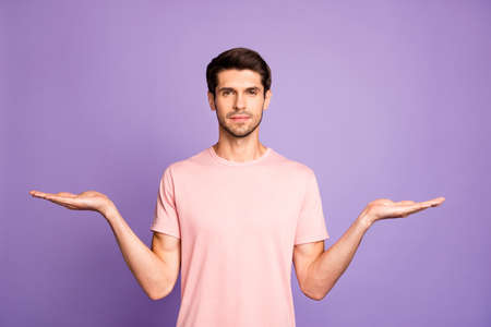 Portrait of his he nice attractive calm content bearded brunet guy wearing pink tshirt holding invisible objects on palms copy space isolated on violet purple lilac pastel color background