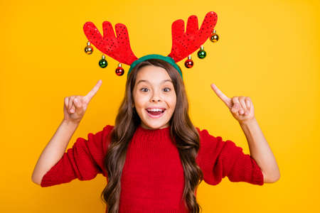 Portrait of excited funny funky brunette wavy hair schoolchild point index finger her christmas theme costume rudolf deer headband mask scream wowe emotions isolated yellow color background