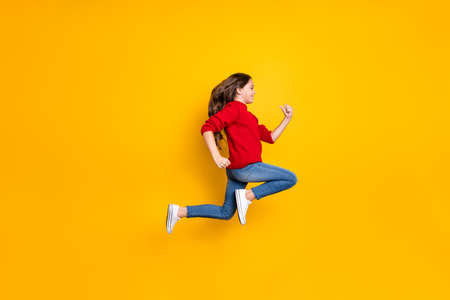 Full length profile side photo of positive cheerful brunette wavy curly hair kid jump run fast speedy after winter season discounts wear style clothes white sneakers isolated yellow color background