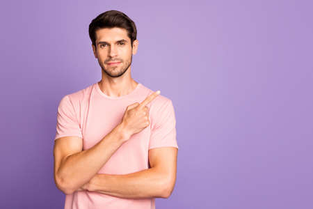 Portrait of his he nice attractive handsome brunet bearded guy wearing pink tshirt pointing forefinger aside follow subscribe isolated over violet purple lilac pastel color background Banque d'images