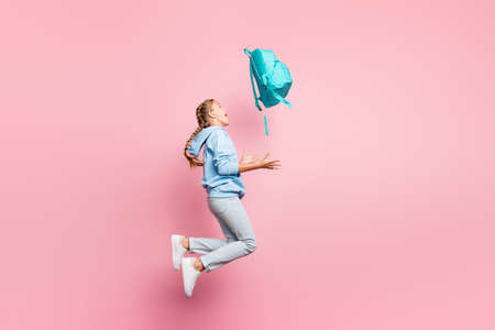 Full body profile photo of pretty little lady jumping high go home after, studying week throwing pupil backpack up air wear casual sweater clothes isolated pink color background