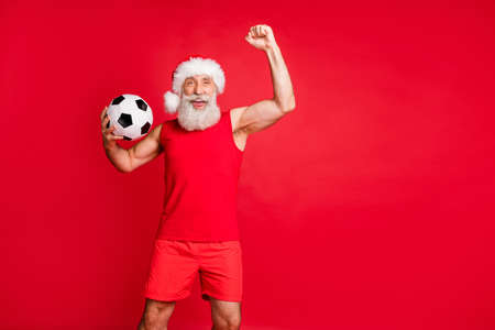 Portrait of crazy fan santa claus in hat cap screaming yes raising fists holding, ball see teams goal wearing sportswear isolated over red background