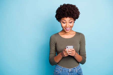 Portrait of amazed funky mulatto girl use her smartphone read feednews, got like from favorite blogger feedback scream wow omg wear green stylish pullover isolated over blue color background