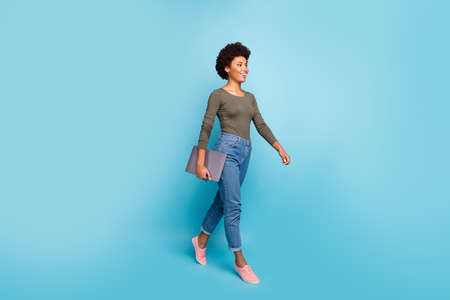 Full length photo of positive cheerful afro american girl hold her netbook go university for education, learning wear casual style outfit denim jeans pink sneakers isolated blue color background