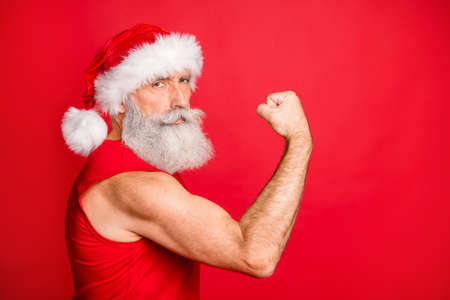 Portrait of confident santa claus show his trainign his triceps wearing, trendy sportswear hat cap isolated over red background