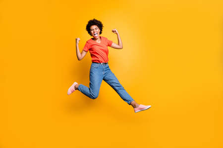 Full length photo of crazy ecstatic girl raise her fists scream shout yeah celebrate victory lottery discounts jump wear red t-shirt trendy, denim jeans sneakers isolated over yellow color background