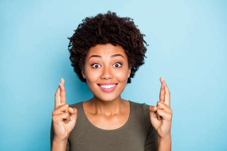 Close up portrait of charming funny cute sweet attractive girlish lady with fingers, crossed staring at you expecting with pleading face expression isolated over blue bright color background